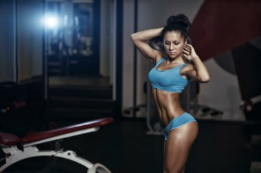 Brunette sexy fitness girl in blue sport wear with perfect body in the gym posing before training set