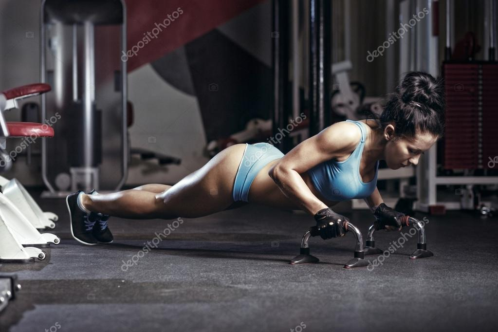 Fitness woman doing push up in the gym. Brunette fitness girl in blue sport wear with perfect body performing push ups