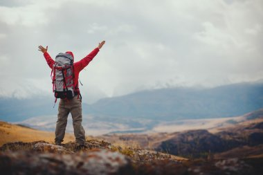 Adventure, travel, tourism, hike and people concept - man with backpack in mountain