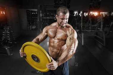 Athlete training with weight in gym