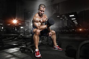 Athlete in the gym training with dumbbells