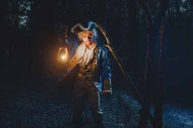 Man dressed as a courtier or officer 17-18 age in night forest.