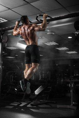 Muscle athlete man in gym making elevations. Bodybuilder trainin