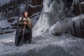 Fotografie Medieval knight with sword in armor as style Game of Thrones in