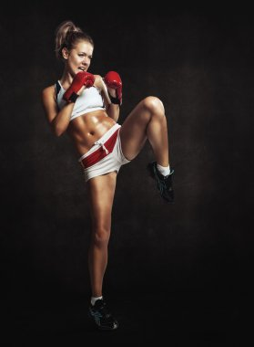 Beautiful athletic girl with boxing gloves hit high foot. Grunge
