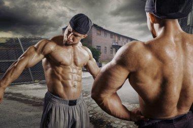 Pumped athlete bodybuilder in ghetto street