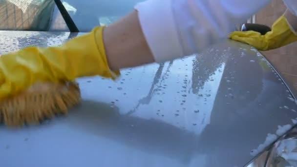 Zenske ruku v žluté rukavice mytí auta