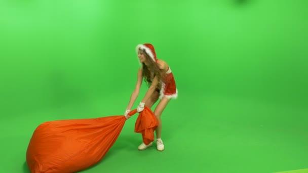 Žena vleče po zemi těžký pytel s dárky