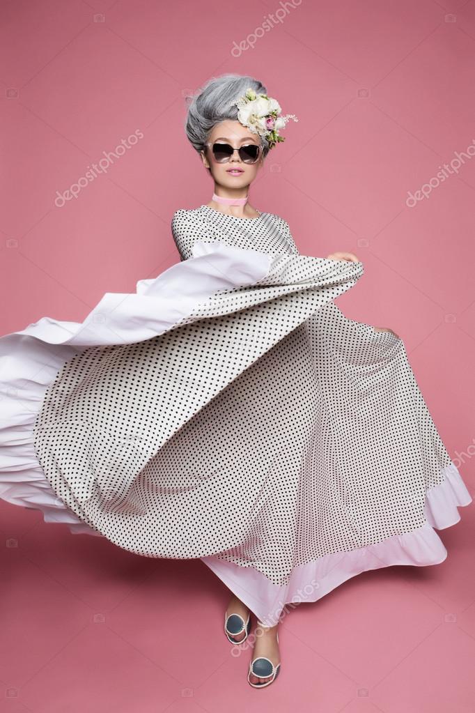 8a9ecab9b0c8 Dynamické fotografie krásná princeznička v dot šaty na měkké růžové pozadí.  Květy jsou na hlavu. Bílá šedé vlasy a sluneční brýle — Fotografie od ...