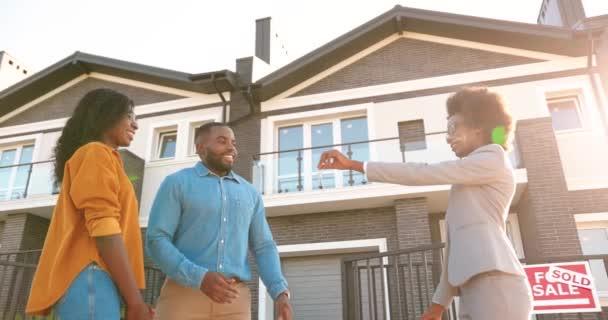 Immobilienmaklerin verkauft Haus an afroamerikanisches Paar und übergibt Schlüssel. Draußen. Freudige verheiratete Männer und Frauen, die sich umarmen und ein Haus am Stadtrand kaufen. Wohnen im Vorort Blick von unten