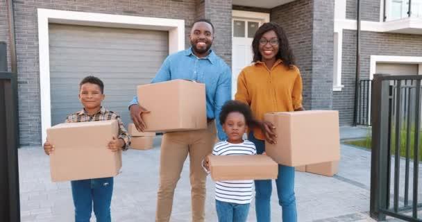 Porträt einer glücklichen afroamerikanischen Familie mit kleinen Kindern, die vor einem neuen Haus am Stadtrand steht und mit Kartons in der Hand lächelt. Fröhliche Eltern und Kinder beim Einzug in ein neues Zuhause. Siedlung am Stadtrand.