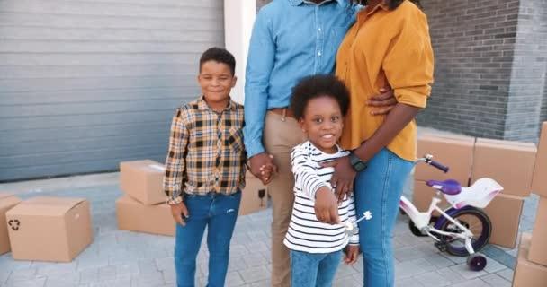 Portrét šťastné afroamerické rodiny s malými dětmi v novém domě na předměstí s úsměvem. Krabice na pozadí. Veselí rodiče a děti se stěhují do nového domova. Osídlení v okrajových oblastech.