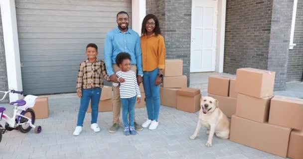 Portrét šťastné afroamerické rodiny s malými dětmi stojící v novém domě na předměstí. Labradorský pes. Veselí rodiče a děti se stěhují do nového domova. Osídlení na předměstí. Prodáno.