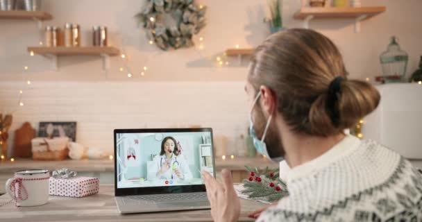 Blick über die Schultern eines kaukasischen Mannes in medizinischer Maske, der in der Weihnachtszeit eine Online-Videokonferenz auf seinem Laptop mit einer schönen Ärztin in Quarantäne hat. Video-Beratung am Computer