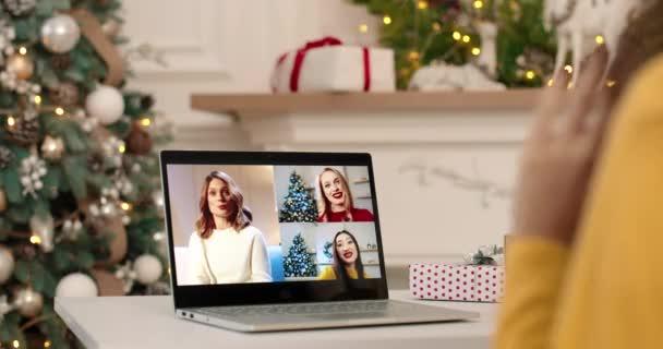 Zavřít. Žena mluví na více videohovory na notebooku s veselými kavkazskými přáteli na Silvestra ve slavnostní náladě. Žena mává rukou a mluví s různými lidmi na počítači
