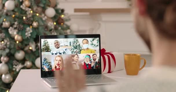 Großaufnahme des Laptop-Bildschirms auf dem Tisch mit mehreren Online-Telefonaten zwischen fröhlichen Freunden gemischter Rassen und dem Weihnachtsmann, der über Weihnachten spricht. Mann plaudert in der Silvesternacht mit verschiedenen Personen