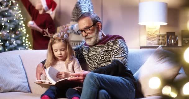 Glücklicher alter Großvater, der auf dem Sofa mit dem kleinen süßen Mädchen sitzt und seiner Enkelin zu Hause Buch vorliest, während sein Sohn und Enkel im Hintergrund den Weihnachtsbaum schmücken. Frohe Feiertage