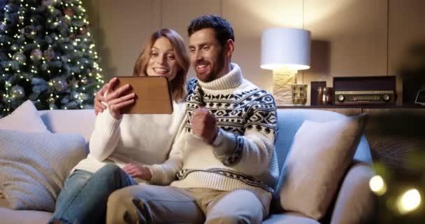 Radostně se usmívající kavkazský pár hovořící na videokonferenci on-line na tabletu s přáteli, zatímco sedí v útulné místnosti s vánoční stromeček na Silvestra. Manžel a manželka mluví na video na zařízení