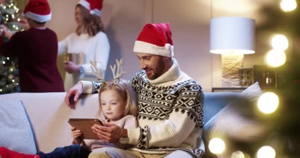 Portrait of caring Caucasian dad in santa hat with cute little girl sitting in room tapping on tablet buying xmas gifts on internet Mom and son decorating glowing Christmas tree Family holiday concept