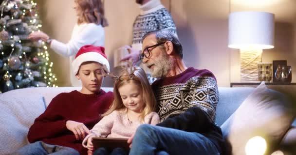 Porträt der kaukasischen niedlichen kleinen Kinder mit Opa reden und tippen auf dem Tablet online sitzen zu Hause an Heiligabend, während Eltern schmücken Weihnachtsbaum auf Hintergrund Frohe Feiertage Konzept