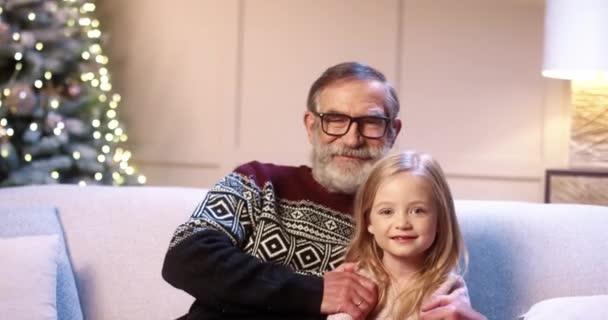 Nahaufnahme Porträt der fröhlichen kaukasischen Familie alten Opa mit niedlichen kleinen Mädchen sitzt in geschmückten Raum in der Nähe von Weihnachtsbaum lächelnd und umarmt an Silvester. Winterurlaub. Weihnachtskonzept