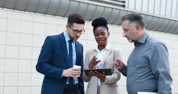Afroamerikanische junge Geschäftsfrau und zwei kaukasische Geschäftsleute stehen an der Straße und diskutieren die Arbeit mit Tablet-Geräten in der Hand. Mixed-Rennen Frauen und Männer sprechen über Arbeitsprojekt.