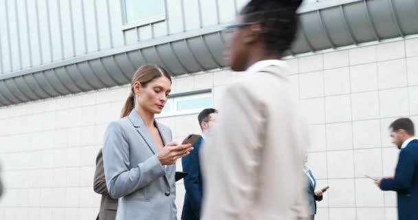 Kaukasische Geschäftsfrau, die mit dem Smartphone in der Hand über die Straße läuft. Gemischte Rennen Männer und Frauen Fußgänger, die im Freien spazieren und Geräte verwenden. Multiethnische Geschäftsleute eilen zur Arbeit in die Stadt.