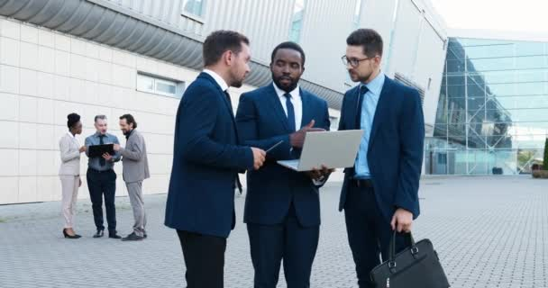 African American and Caucasian businessmen standing at street at business center and discussing work with laptop computer in hands. Multi ethnic men partners talking about working project. Discussion.