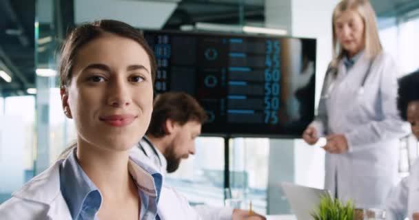Nahaufnahme Porträt einer glücklichen jungen Ärztin, die in die Kamera blickt und lächelt, während sie auf einer Konferenz mit Ärzten verschiedener Rassen sitzt, die Statistiken über Covid-19 diskutieren. Coronavirus-Pandemiekonzept