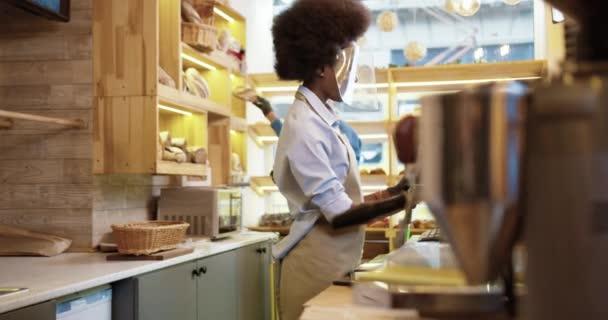 Oldalnézet afro-amerikai csinos nő eladó áll a pultnál bakehouse arcvédő és kesztyű kopog a számítógép dolgozik pékségben. A férfi munkatárs a háttérben dolgozik. Üzleti koncepció