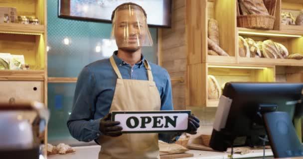 Porträt eines fröhlichen afroamerikanischen jungen Mannes mit schützendem Gesichtsschutz und Handschuhen in der Hand, der in der Backstube steht. Bäckermeister eröffnet Bäckerladen wieder Konzept für Kleinunternehmen