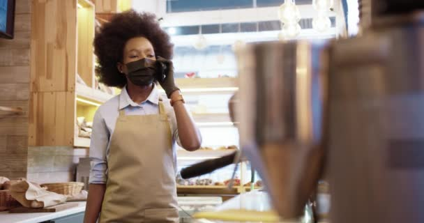 Beautiful African American young woman seller in bakery shop standing indoor and talking on cellphone. Female bakehouse worker speaking on smartphone in own small coffee shop. Job concept