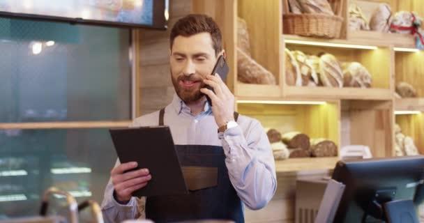 Porträt eines glücklichen kaukasischen bärtigen, gutaussehenden Bäckers, der in seiner eigenen Bäckerei steht, auf einem Tablet tippt und mit dem Smartphone spricht. Männlicher Arbeiter im Gespräch am Handy mit dem Kunden. Backhauskonzept