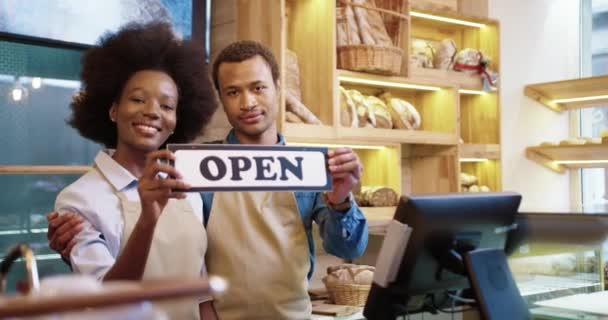 Portrait of cheerful young African American family married couple of bakers in aprons reopening bakehouse holding Open sign in hands. Small own bakery shop. Business concept