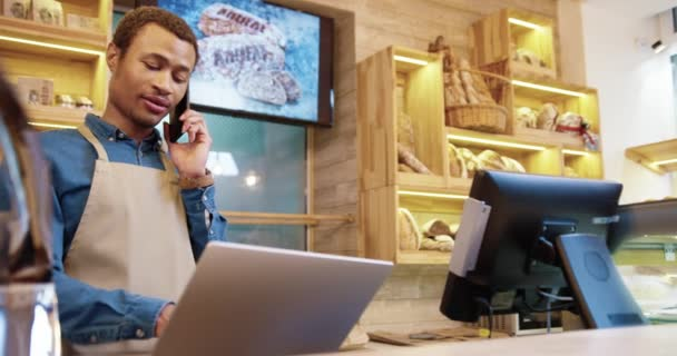 Close up of handsome happy man owner of bakery store standing in bakehouse indoors speaking on smartphone and typing on laptop at work in good mood taking order over cellphone. Business concept