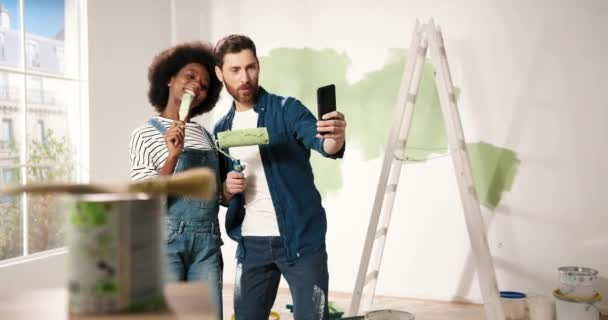 Joyful mixed-races young family couple wife and husband smiling posing with brushes taking selfie photos on smartphone in room. Home repair concept. Man and woman taking pictures during renovation