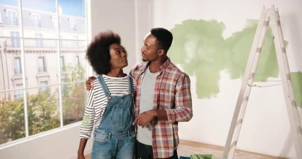 Glückliches junges afroamerikanisches Paar steht in einem Zimmer in einer neuen eigenen Wohnung und diskutiert über Design und Einrichtung des Hauses. Ehefrau im Gespräch mit Ehemann über Reparatur zu Hause. Sanierung und Verbesserung des Wohnungskonzepts