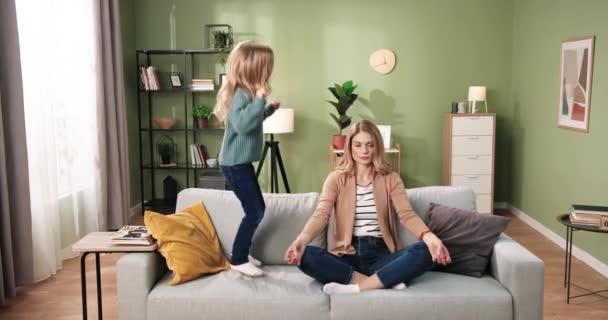 Kaukasische schöne junge Frau sitzt auf dem Sofa und praktiziert Yoga, meditiert mit ruhigem, entspanntem Gesicht, während ihre kleine süße Tochter auf der Couch im Haus springt. Entspannung. Mutterschaftskonzept
