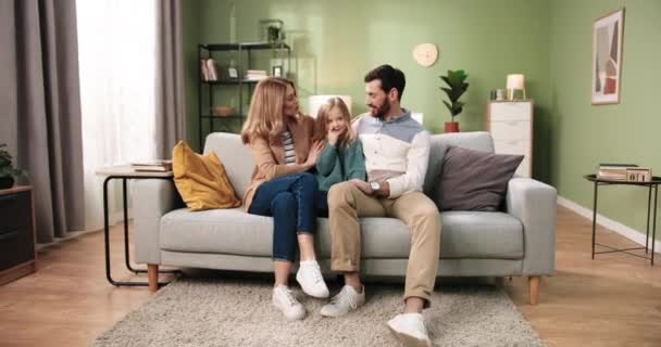 Happy smiling Caucasian parents with little cute daughter sitting on sofa in cozy living room at home speaking and spending family time together. Mom and dad with small child. Love and care concept