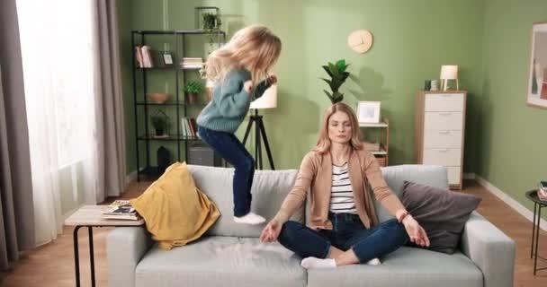 Kaukasische junge hübsche Mutter sitzt auf der Couch und praktiziert Yoga und meditiert mit ruhigem Gesicht, während ihre kleine süße Vorschultochter zu Hause auf dem Sofa springt. Entspannungs- und Ruhekonzept