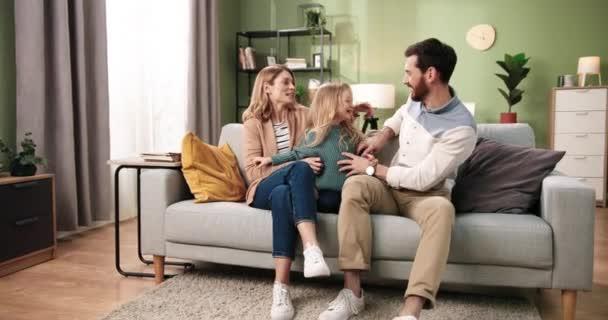 Kaukasische fröhliche junge Eltern haben Spaß, ruhen sich aus, verbringen Zeit mit der Familie, kitzeln ihre kleine süße Tochter, lachen und lächeln im Wohnzimmer auf dem Sofa sitzend. Glückskonzept