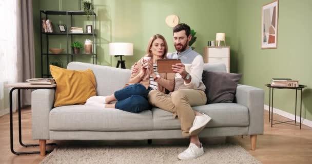 Šťastný mladý ženatý kavkazský pár hledá internetový prohlížení on-line nákup na tablet zařízení sedí na pohodlné pohovce spolu. Manžel pomocí gadget mluvit s manželkou, která pije kávu odpočinku