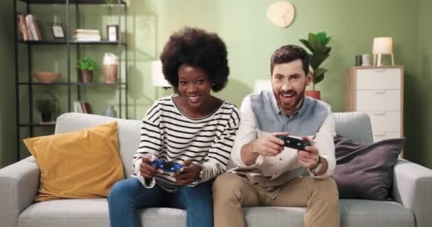 Vidám vegyes rasszú pár afro-amerikai nő és kaukázusi férfi pihen a szobában ül a kanapén és videojátékozik joystickokkal. A barátok jól érzik magukat otthon. Játékosok koncepciója