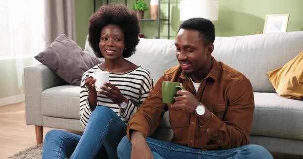 Nice lovely African American joyful married family couple man and woman sitting on floor, resting, drinking hot coffee or tea and speaking in good mood. Family leisure concept. Happy together