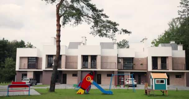 Elite real-estate buildings and playground for kids. Houses at suburbs. Nice semi-detached homes. Place for playing with children at building. Outskirts.
