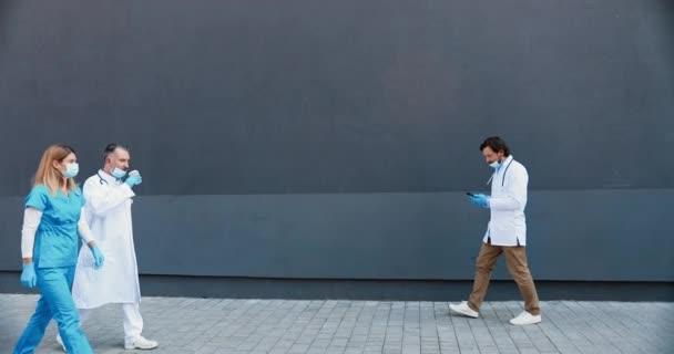 Gemischte Rassen Männer und Frauen Ärzte in weiß-blauen Gewändern und medizinischen Masken gehen im Freien hin und her. Multiethnische Sanitäter treten und sprechen. Kommunikation im Krankenhaus.