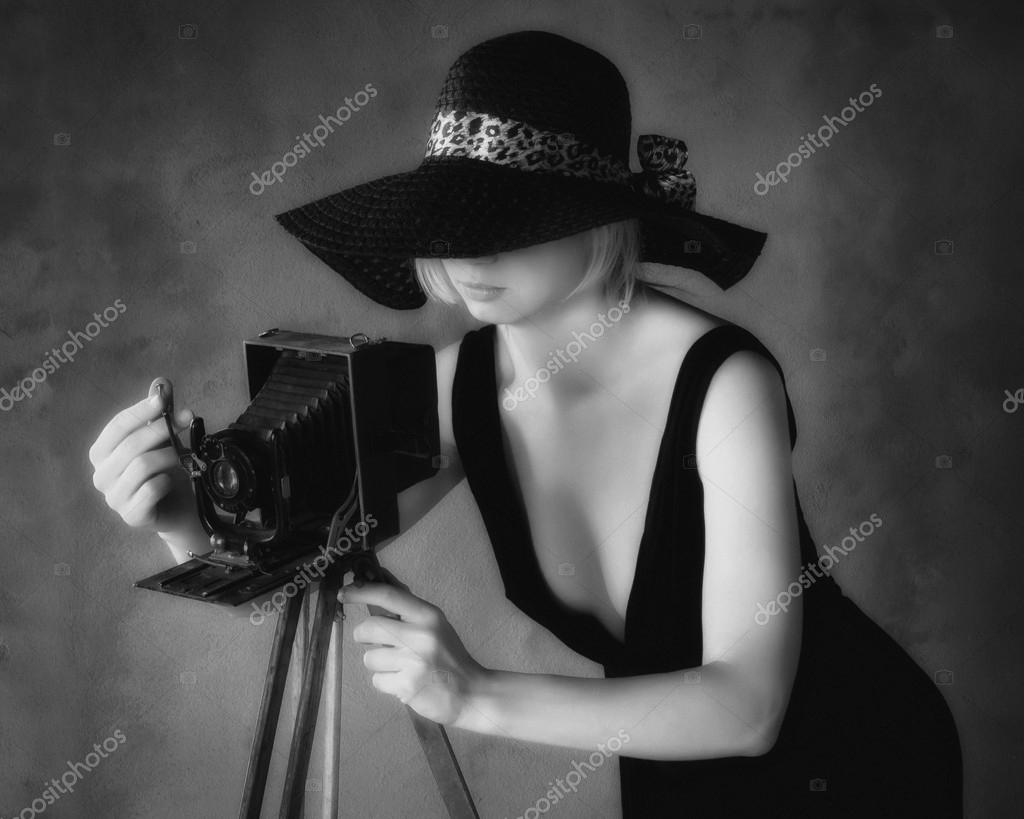Girl photographer in a black hat with an old camerablack and white image de sergeka