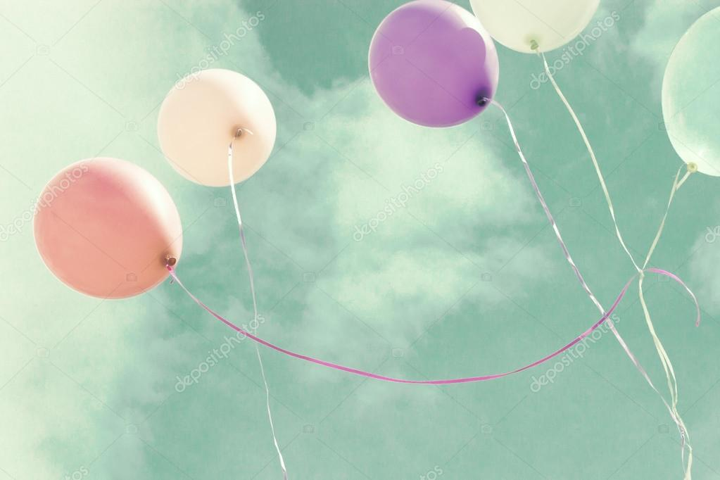 Colorful balloons over vintage sky