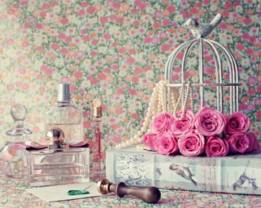 Birdcage with peonies on book and perfumes
