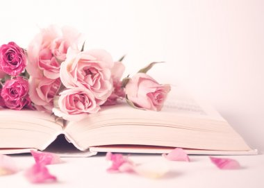 Pink peonies and roses on book